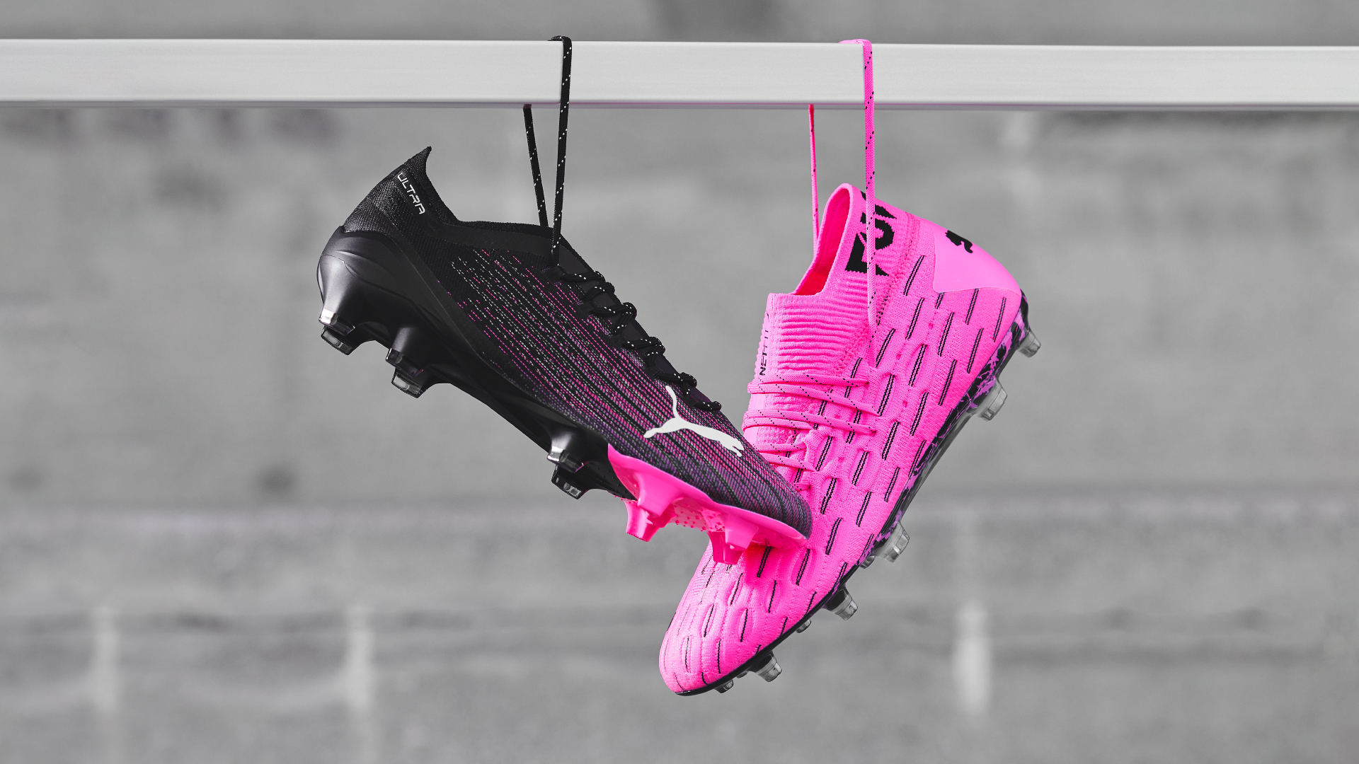 Puma Ultra 1.1 black boot hanging off crossbar with a pink Puma Future 6.1 boot.